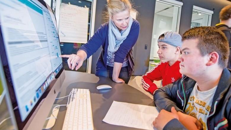Da qualmen die Köpfe: Tina Nöcke hilft Nabil und Ömer beim Kalkulieren von Personalkosten und Investitionen. Foto: Straßmeier