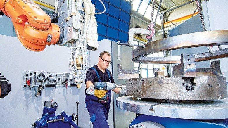 Gleich legt hier der Roboter los: Dominik Schmitt richtet eine Anlage ein, in der eine Schutzschicht auf Stahlteile kommt.