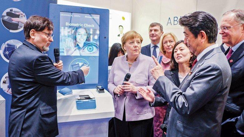 Hoher Besuch: Dermalog-Chef Günther Mull (links) mit Japans Premierminister Shinzo Abe (vorne rechts) und Kanzlerin Angela Merkel auf der Cebit-Messe.