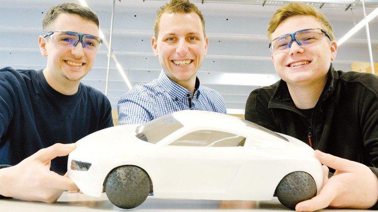 Modellauto mit Kugelreifen: Daniel Breidenstein, Ausbildungsleiter Stefan Grünewald und Luca Pfeiffer (von links).