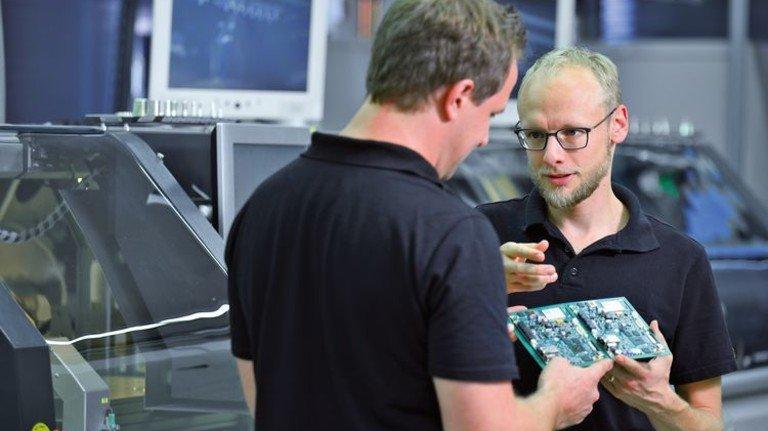 Fachlicher Austausch: Arne Dethlefs begutachtet mit einem Kollegen eine Leiterplatte. Foto: Augustin