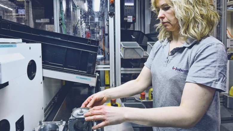 Im Norden hat die Zukunft begonnen: Ramona Gartmann legt für einen Fertigungsroboter Gebläseteile auf. Foto: Christian Augustin