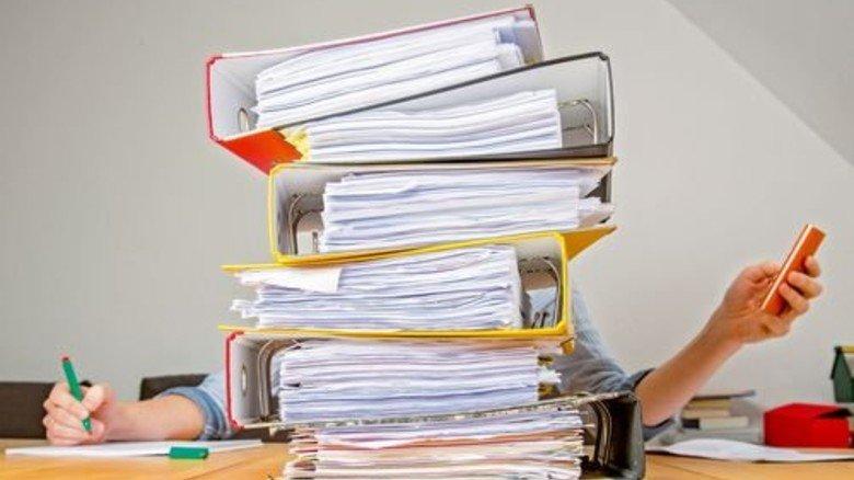 Aktenstapel: Immer mehr Mitarbeiter in den Firmen verbringen ihre Zeit mit Dokumentation. Foto: Mauritius