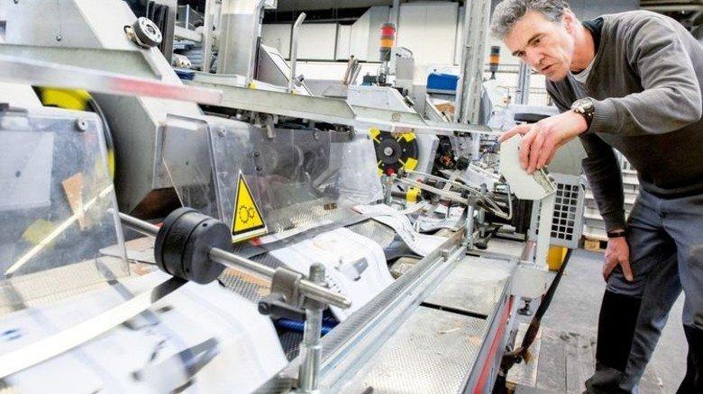 Bedienung: Maschinenführer Norbert Müller zeigt, wie Flyer in eine Zeitschrift eingelegt werden. Foto: Straßmeier