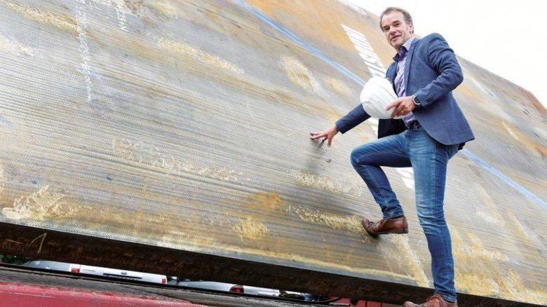 Daraus werden Rohre: Wolfgang Schlemper, Vertriebsmann der Firma Eisenbau Krämer, zeigt dem AKTIV-Fotografen eine Stahlplatte. Foto: Wirtz