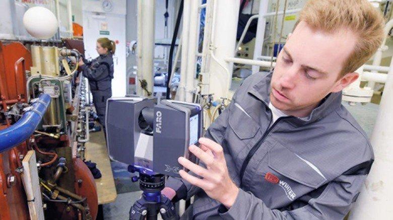 Vorbereitung: Jan Hagemeister richtet den Laser ein, seine Kollegin Franziska Reimler hat links bereits eine weiße Referenzkugel gesetzt. Foto: Augustin