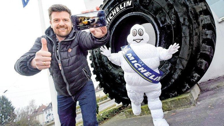 Vor einem der größten Reifen der Welt: Benjamin Rütschle und das Michelin-Männchen.