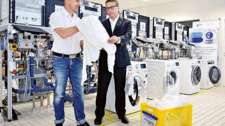 Handarbeit: Prüfingenieur Ralf Geisel und Niedziella im Waschmaschinen-Testlabor. Foto: Scheffler