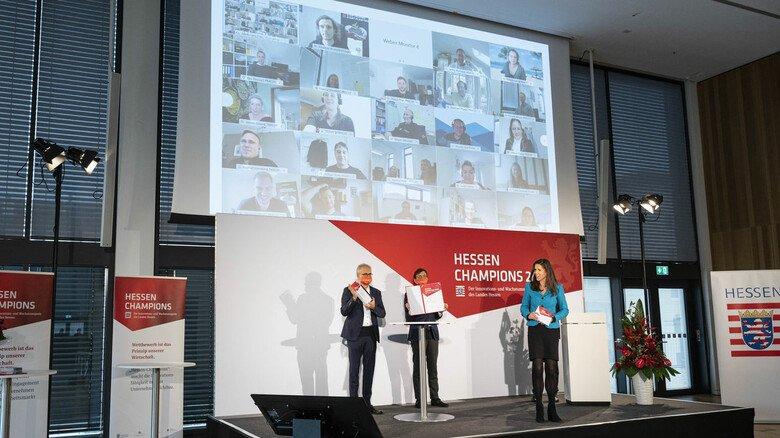 Jubel bei den Beschäftigten von Alfred PRACHT Lichttechnik über den Sieg in der Kategorie Innovation – wenn auch aus der Ferne. Auf der Bühne gratulieren Tarek Al-Wazir, Wolf Matthias Mang und Moderatorin Corinna Egerer (von links).