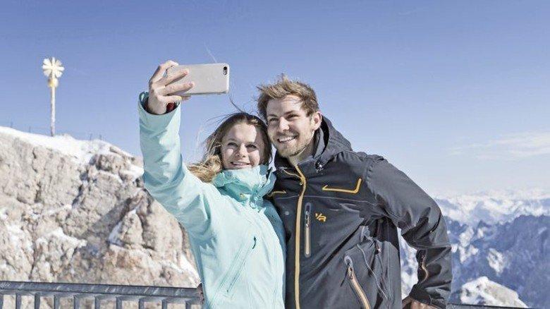 Foto mit Gipfelkreuz: Deutschlands höchster Berg ist ein Ausflugsmagnet nicht nur für Skifahrer. Foto: Bayerische-Zugspitzbahn-Bergbahn-AG/Matthias Fend