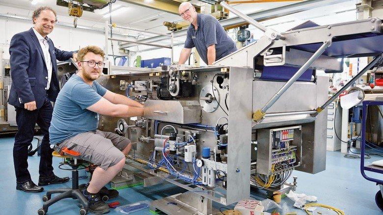Endmontage eines Gebäckformers: Matthias Drees, Geschäftsführer bei OKA in Darmstadt, im Gespräch  mit dem Elektriker Sebastian Weber und dem Industriemechaniker Norbert Pschorn (von links)