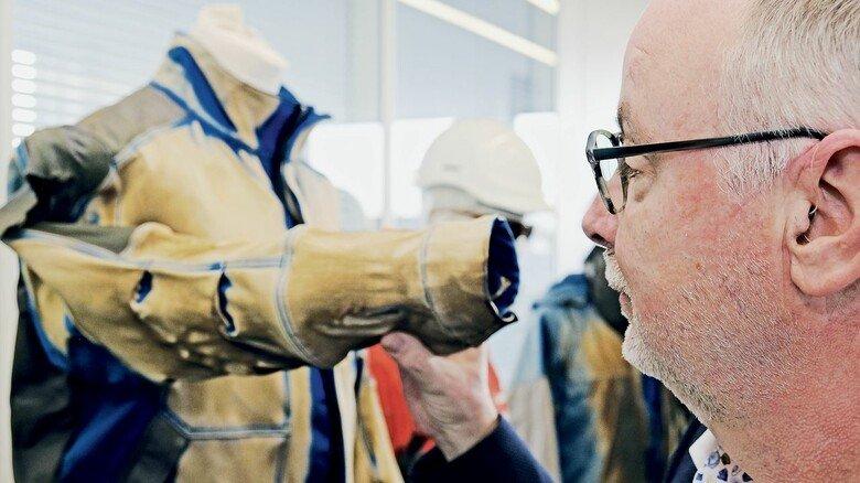Blick in den Showroom: Siegfried Kiewitt mit einer im Feuer getesteten Jacke, die mit einem Hitzeschutz ausgerüstet ist.