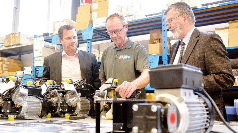 Im Betrieb: Sven und Albrecht Hallbauer mit Produktionsmitarbeiter Frank Müller, der eine Öl-Pumpe montiert.