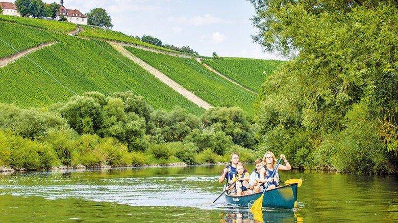 Gemütlich: Eine Bootstour mit der Familie – vorbei an den Weinbergen am Main. Foto: Franken Tourismus Hub