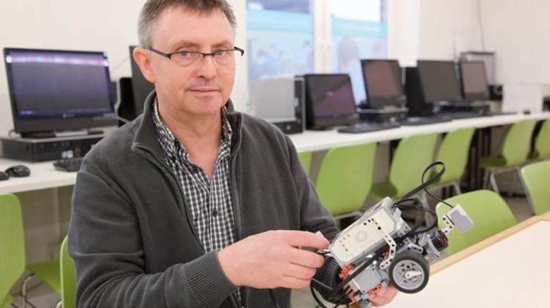 Spielerisch: Gerd Iffland mit einem Mindstorms-Roboter von Lego. Foto: GuS Kommunikation