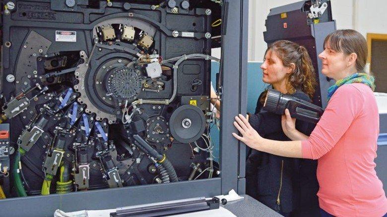 Ausbildung: Druckerin Susanne Greß und Azubi Anna Dakun (links) rüsten eine digitale Bogendruckmaschine. Foto: Scheffler