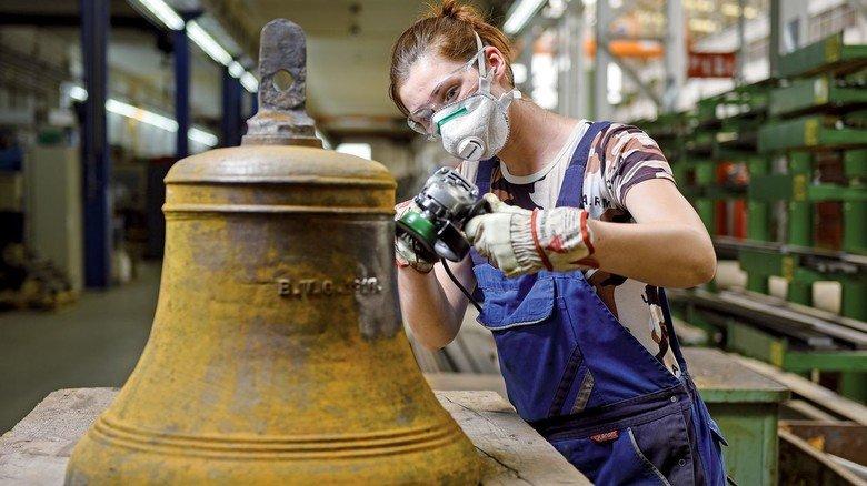 """Klangkörper: Die Glocke der """"Amrumbank"""", die EWD-Mitarbeiterin Sonja van Hettinga hier säubert, wurde im Stahlformguss hergestellt."""