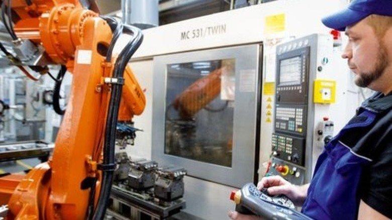 Automatisierte Produktion: Sascha Birker programmiert einen Roboter. Foto: Stoppel