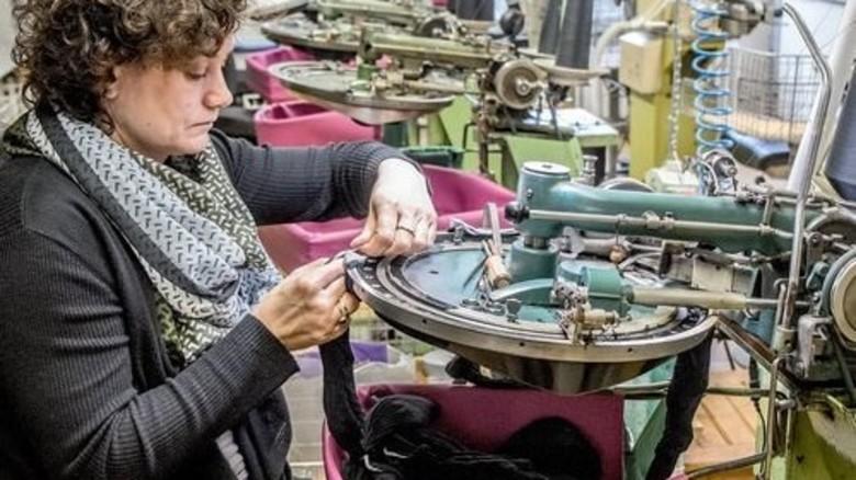 Handarbeit im Minutentakt: Silvia Buhl zieht einen Strumpfschlauch auf die Kettelmaschine. Foto: Roth