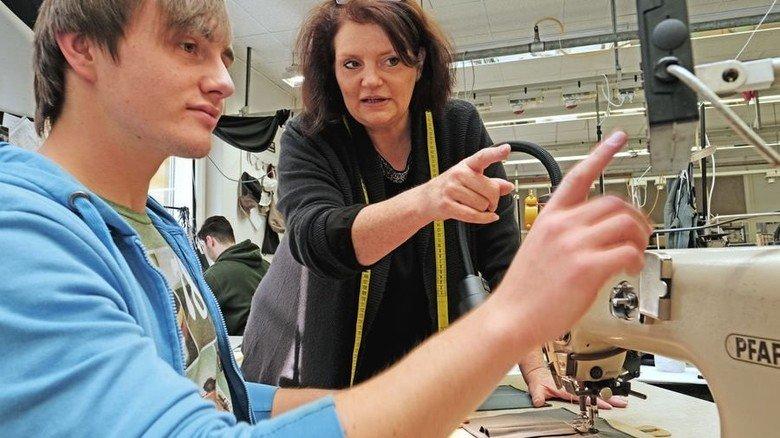 Fragen willkommen: Die Ausbildungsleiterin erklärt dem Azubi Michel Imorde die Arbeit an der Nähmaschine. Foto: Lang