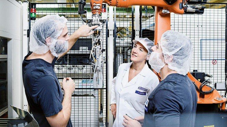 Moderne Produktion in Leutkirch: Ausbilder Daniel Motz, Vera Kowitz, Mitglied der Geschäftsleitung, und Maschinenführer Ali Doganay (von links) an einem Roboter, der Verpackungen in Transportkisten setzt.