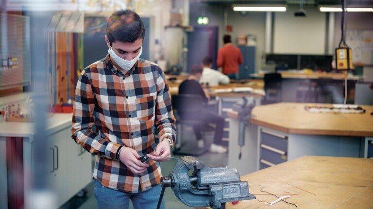 Besondere Bedingungen: Auszubildende arbeiten am Schraubstock bei offenem Fenster – Corona Schutzmaßnahmen im Unterricht in der Berufsschule.