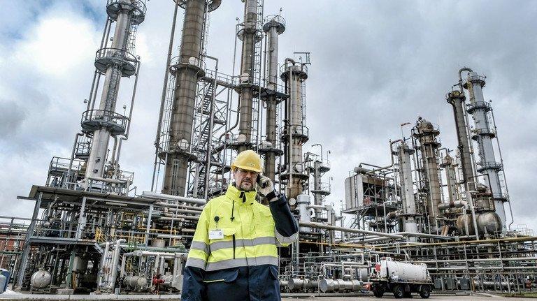 Vernetzt: Standortleiter Henning Wartig hat die gesamte Produktion im Blick – auch die Destillationskolonnen im Hintergrund.