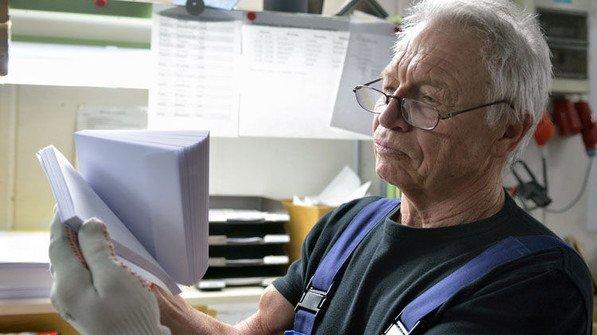 Geschultes Auge;: Pensionär Wilhelm Zangler bei einer Sichtkontrolle von Kuverts. Er arbeitet noch stundenweise im Betrieb. Foto: Scheffler
