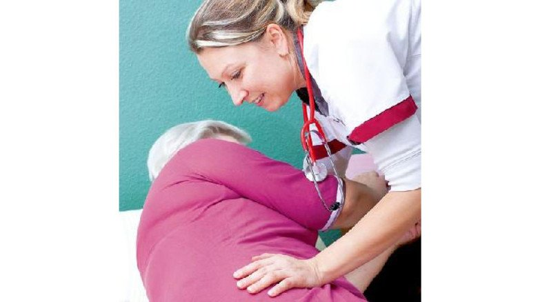 Hier ist Kraft gefragt: Eine Pflegerin hilft beim Aufstehen. Foto: Panthermedia