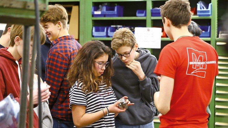 Technik zum Anfassen: Zwei Schüler betrachten mit Argusaugen ein gefrästet Werkstück.