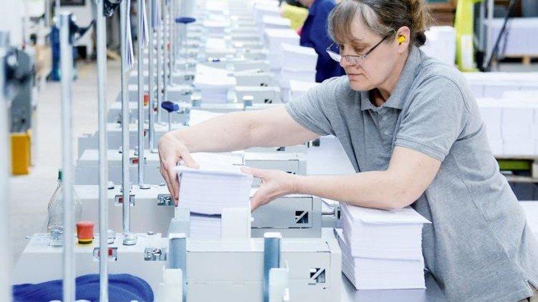 Produktion: Heike Höfig beim Einlegen von Bögen, aus denen Bücher werden. Foto: Sturm