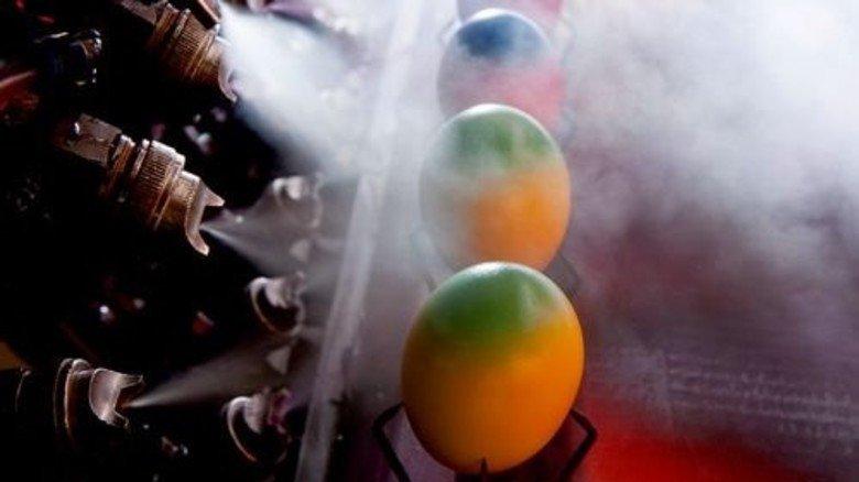 Am Fließband: Gleich vier Düsen besprühen die Eier mit Farbe. Foto: Moll