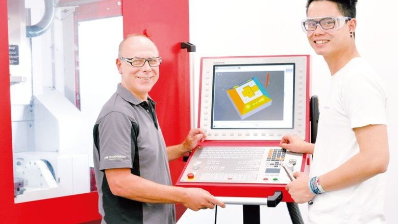 Lernen mit Coach: Azubi Nam Nguyen mit Ausbilder Gerald Bitsch an einer Fräsmaschinensteuerung. Foto: Scheffler