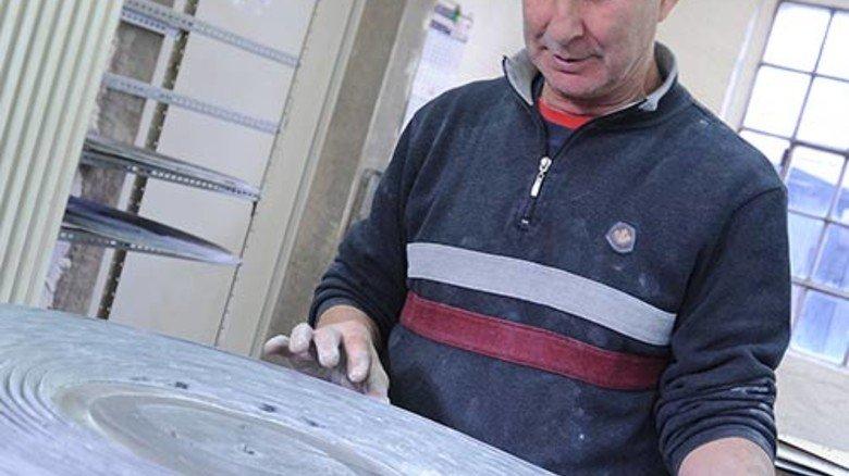 Qualitätskontrolle: Arif Eriten checkt frisch gepresste Profilschnüre auf Unebenheiten und Risse. Foto: Albert