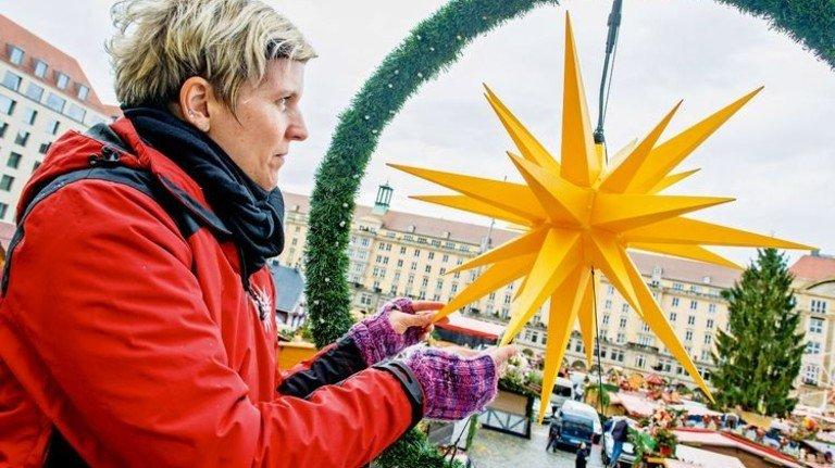 Dresdner Striezelmarkt: Mitarbeiterin Claudia Bachmann prüft den Stern einer Lichterkette. Foto: Straßmeier