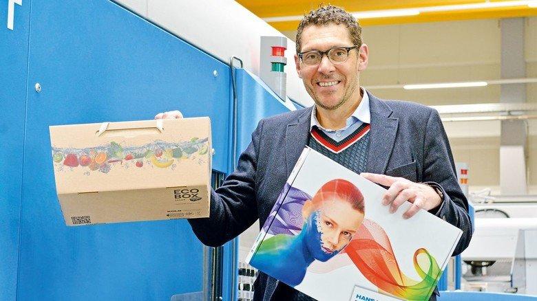 """Leuchtende Farben: Marketingchef Thomas Wund mit einem Musterkarton und einer """"Eco-Box"""" für Supermärkte."""