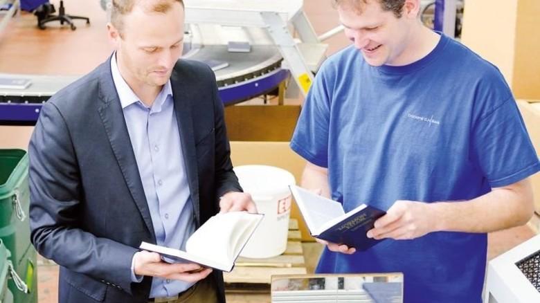 Optische Prüfung: Waldemar Pflaum (links) und ein Kollege begutachten fertige Bücher. Foto: Scheffler