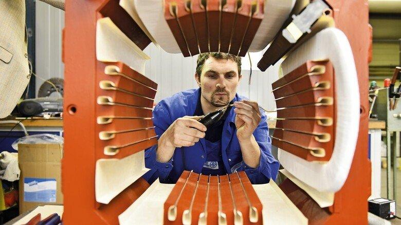 Wartung: Michael Marek am Gehäuse eines großen Elektromotos, der komplett zerlegt wurde und nun instandgesetzt wird.