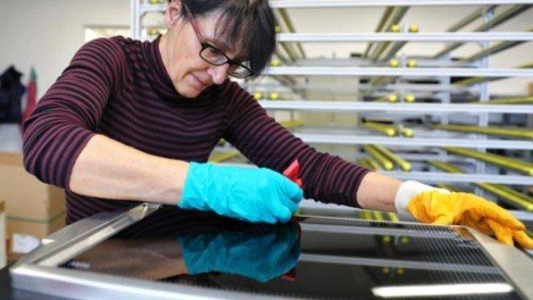 Handarbeit: Hier werden die Glasplatten auf die Ceran-Kochfelder geklebt. Foto: Karmann