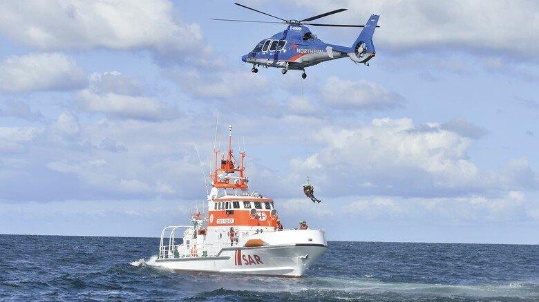 """Gerettet: Die Hubschrauber-Besatzung setzt eine Person per Winde auf dem Rettungskreuzer """"Theo Fischer"""" ab."""