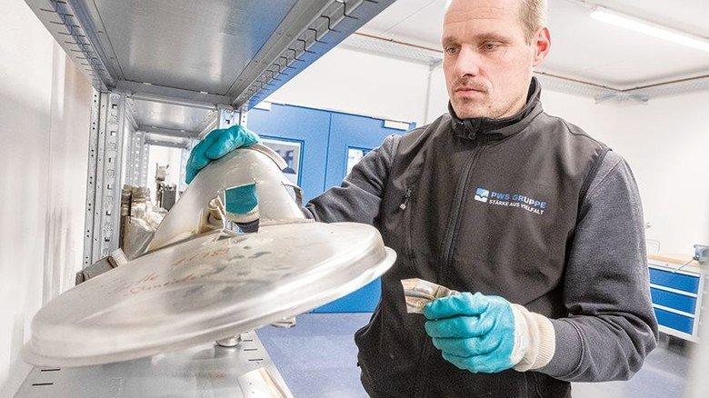 Mit Bauteil für ein Abgassystem: Der angehende Qualitätsprüfer Meyer beim Autozulieferer PWS. Foto: Roth