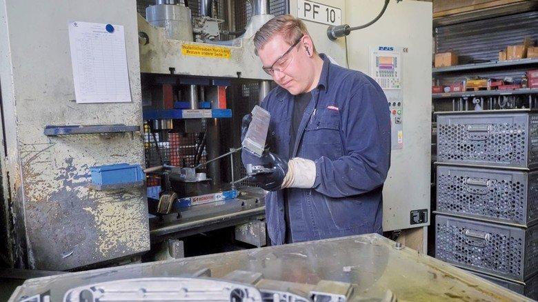 Hohe Qualität für Medizintechnik, Auto- und Flugzeug-Industrie: Timo Rieckmann bei der Sichtkontrolle an der Entgratpresse.