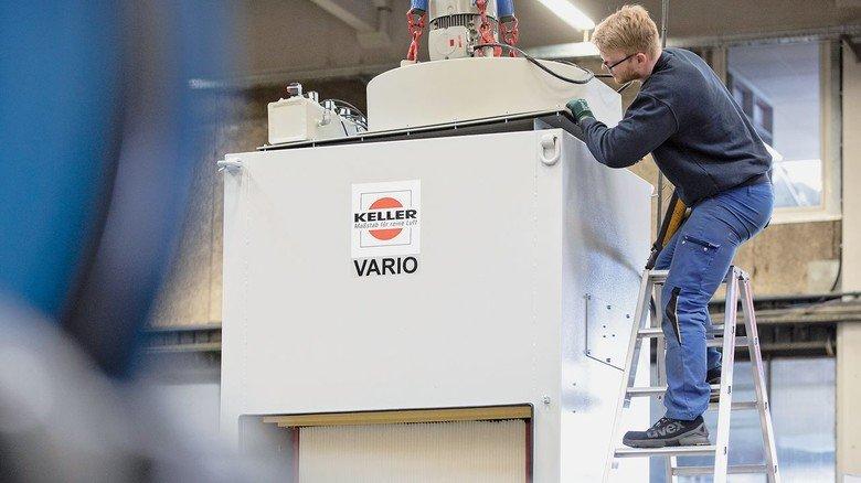 Hier muss jetzt alles perfekt passen: Ein Keller-Mitarbeiter setzt mithilfe eines  Krans den schweren Motor in eine Absauganlage ein.