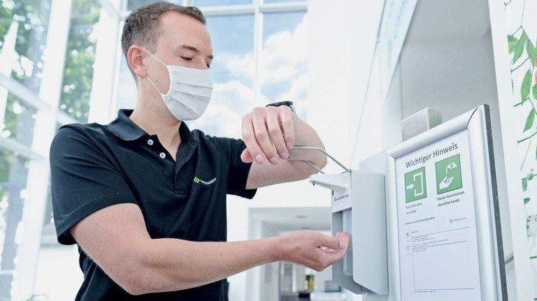 Drinnen lieber mit Maske: Stefan Ruholl desinfiziert sich im Foyer die Hände. Direkt daneben hängen, wie überall im Unternehmen, wichtige Hygienehinweise.