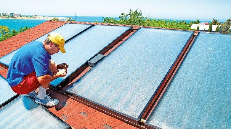 Montage von Sonnenkollektoren: Mit ihrer Energie kann man Warmwasser erzeugen.