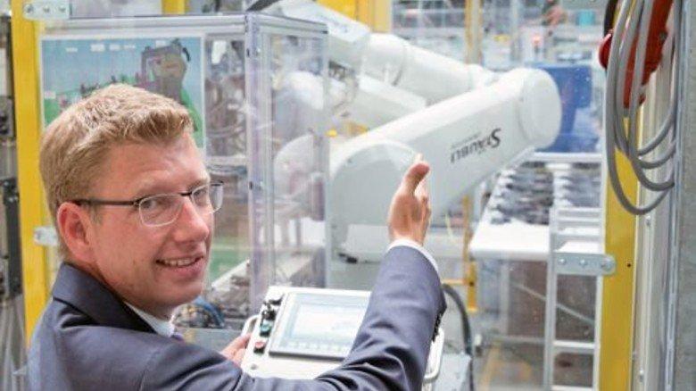 Gestatten: Werkleiter Thomas Lange-Stalinski mit Roboter. Foto: Karmann
