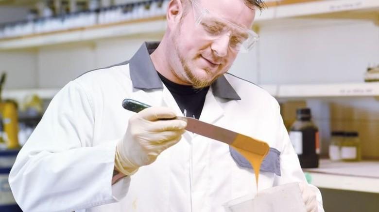 Augenmaß: Laborleiter Bastian Pollak prüft die Viskosität der Farbe. Foto: Peter Wirtz