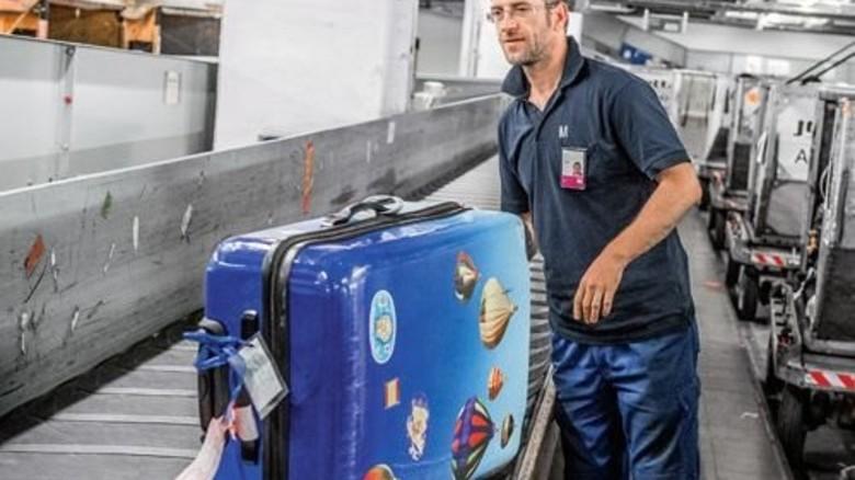 Schwere Lasten: Mitarbeiter am Entnahmekarussell an der Abfertigung. Foto: Roth