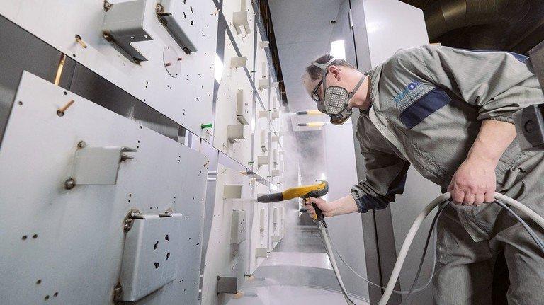 Konzentrierte Arbeit gefordert: Ein Mitarbeiter beschichtet Metallplatten mit elektrostatisch haftendem Pulverlack.