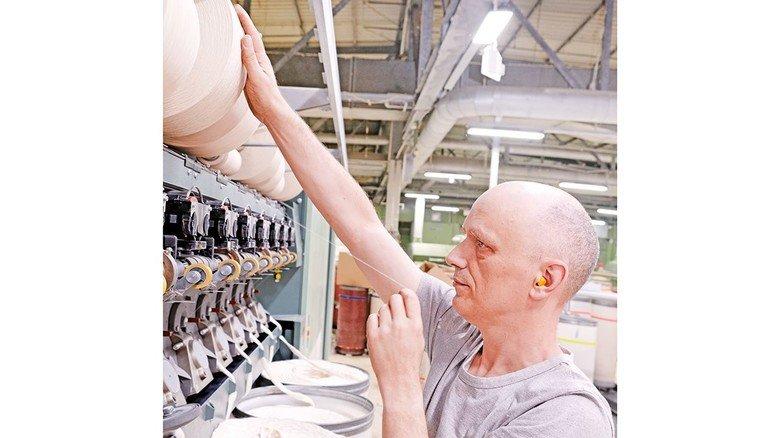 Alltägliche Arbeit: Maschinenführer Stefan Vahling wechselt eine Garnspule in der Spinnerei. Dem Garn ist die recycelte Baumwolle beigemischt.